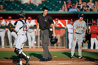 Umpire Jae-Young Kim after calling Morgan McCullough (11) out as catcher Gabriel Moreno (23) holds up the ball during a Midwest League game betwee the Burlington Bees ad Lansing Lugnuts on July 18, 2019 at Cooley Law School Stadium in Lansing, Michigan.  Lansing defeated Burlington 5-4.  (Mike Janes/Four Seam Images)