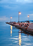 Couples sit on Molo Audace pier at sunset, looking at the Gulf of Trieste, Italy