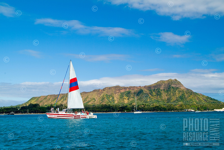 A catamaran cuts a path on the clear blue water in front of Diamond Head,