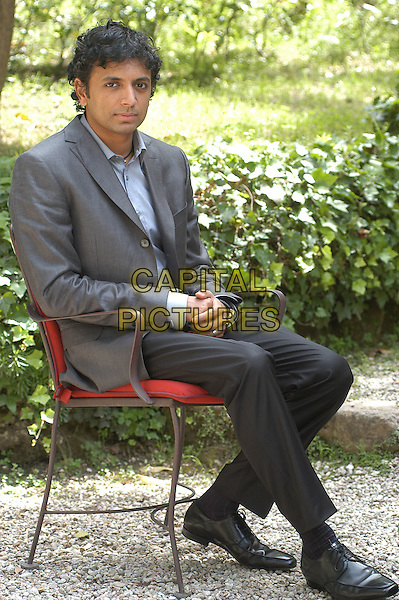 "M. NIGHT SHYAMALAN.Photocall for new film entitled.""E venne il giorno"" ( English translation -The happening ) in Rome, Italy, 26th May 2008..full length sitting in chair gray gray suit jacket .CAP/CAV.©Luca Cavallari/Capital Pictures"