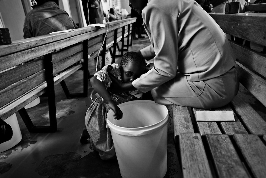 A Zimbabwean child infected with cholera and too weak to stand is helped to its feet by her mother at the Budiriro Polyclinic which is being used as a Cholera Treatment Clinic in Budiriro, Zimbabwe, Friday, December 19, 2008.