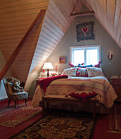 This newly built bedroom has a much older traditional feel, with its vaulted ceiling and floral bed cover and cushions