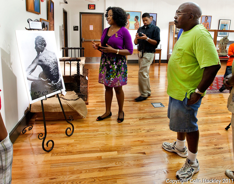 TALLAHASSEE, FLA. 7/15/11-VFBA071511 CH-Tanisha Matthews, second from left, talks about the photo of a whip-scarred slave Gordon while Studson Jefferson, Jr. of Atlanta, Ga. right, listens as during a tour for the Robinson Family Reunion through the Slavery in the Old South collection at the Black Archives Research Center on the campus of Florida A&M University July 15, 2011 in Tallahassee, Fla..COLIN HACKLEY PHOTO