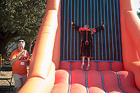 Tom Kosakowski '88 takes photos as his daughter, Emily Fishbach, tries out the velcro wall. Occidental College celebrates Homecoming and Family Weekend on Saturday, Oct. 14, 2017 at Oswald's Homecoming Party in the Academic Quad, featuring games, activity booths, a pub and food.<br /> (Photo by Marc Campos, Occidental College Photographer)