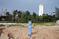 A woman prays on the shores of Dongting Lake, Hunan Province. Dongting Lake has decreased in size in recent decades as a result of land reclamation and damming of the Yangtze. China. 2010