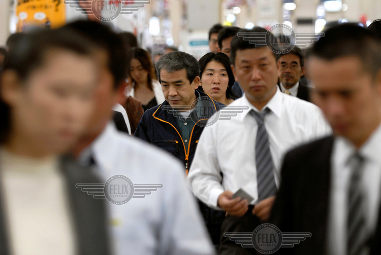 A cross-section of typical commuters/salarymen on their way to work at Osaka central train station.