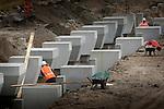 UTRECHT - Op knooppunt Oudenrijn plaatsen medewerkers van Heijmans Infrastructuur betonkoppen op de onlangs geslagen heipalen als onderdeel van een nieuw, experimenteeel wegdek, ModieSlab. Het door Heijmans Infrastructuur, Betonson en ingenieursbureau Arcadis ontwikkelde wegdek bestaat uit een prefab-betonplaat met een toplaag van 'zeer open cement beton' die op een fundering van palen wordt gelegd.  Het wegvak wordt als proef aangelegd in opdracht van Rijkswaterstaat's project Wegen naar de Toekomst, en moet aantonen dat snelwegen niet alleen sneller kunnen worden aangelegd maar eveneens geluidsstilller. COPYRIGHT TON BORSBOOM