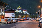 Rinpung Dzong with Paro town at night, Bhutan..Bhutan the country that prides itself on the development of 'Gross National Happiness' rather than GNP. This attitude pervades education, government, proclamations by royalty and politicians alike, and in the daily life of Bhutanese people. Strong adherence and respect for a royal family and Buddhism, mean the people generally follow what they are told and taught. There are of course contradictions between the modern and tradional world more often seen in urban rather than rural contexts. Phallic images of huge penises adorn the traditional homes, surrounded by animal spirits; Gross National Penis. Slow development, and fending off the modern world, television only introduced ten years ago, the lack of intrusive tourism, as tourists need to pay a daily minimum entry of $250, ecotourism for the rich, leaves a relatively unworldly populace, but with very high literacy, good health service and payments to peasants to not kill wild animals, or misuse forest, enables sustainable development and protects the country's natural heritage. Whilst various hydro-electric schemes, cash crops including apples, pull in import revenue, and Bhutan is helped with aid from the international community. Its population is only a meagre 700,000. Indian and Nepalese workers carry out the menial road and construction work.