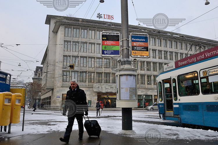 A businessman walks with his luggage in the snow past a tram on Paradeplatz, the symbolic centre of the Swiss banking industry, showing the headquarters of Switzerland's largest bank, UBS, in the background. The Swiss banking industry holds an estimated 4,000 billion Swiss Francs (USD 4,240 billion) in assets, more than half of it foreign, including CHF 880 billion in undeclared European assets alone, benefiting from the country's famous banking secrecy laws.
