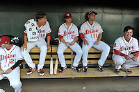 Center fielder Andrew Benintendi (2) of the Greenville Drive (center) sits in the dugout waiting for the start of his first home game against the Greensboro Grasshoppers on Tuesday, August 25, 2015, at Fluor Field at the West End in Greenville, South Carolina. Benintendi is a first-round pick of the Boston Red Sox in the 2015 First-Year Player Draft out of the University of Arkansas. Greensboro won, 3-2. (Tom Priddy/Four Seam Images)