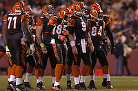 14 November 2004:  Carson Palmer (9), Chad Johnson (85), T. J. Houshmandzadeh (84) and the Cincinnati Bengals offense wait for play to resume.<br />