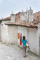 Narrow cobble stone street with traditional ottoman white stone houses. An Albanian flag on the wall. Four stone chimneys. A young woman walking on the street. Berat upper citadel old walled city. Albania, Balkan, Europe.