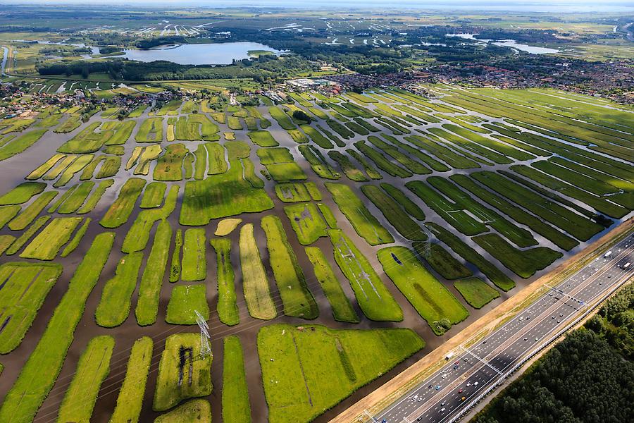 Nederland, Noord-Holland, Gemeente Oostzaan, 14-06-2012; Polder Oostzaan, gezien naar het lintdorp Oostzaan. Achter het dorp de Stootersplas in recreatiegebied Het Twiske. Autosnelweg A9 (ring Zaandam) in de voorgrond. .De verkaveling in het gebied is het resultaat van veenontginning. .Polder and village Oostzaan, north of Amsterdam. The division in plots in the area is the result of peat extraction..luchtfoto (toeslag), aerial photo (additional fee required);.copyright foto/photo Siebe Swart