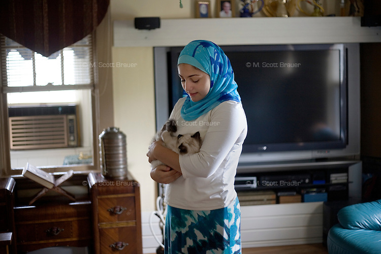 "Shayreen, 16, plays with a kitten at her home in West Warwick, Rhode Island, USA, on Sunday, Aug. 22, 2011.  The family has two adult cats and and two kittens.  Unlike the rest of her family, Shayreen is very devoted to her Muslim faith.  ""I feel it's my responsibility as a Muslim to be a positive role model,"" said Shayreen, ""I see a negative energy toward Muslims in the media.""  Shayreen is will be a high school junior at Lincoln School, an all-girls Quaker school in Rhode Island. The rest of her family is not particularly religious.  When Shayreen began wearing the hijab head covering in her early teens, ""My parents were very supportive, but my aunt tried to talk me out of it. My grandmother was upset.  I was more worried about what my family would think [than what other people would think].""..photo by: M. Scott Brauer for Education Week"