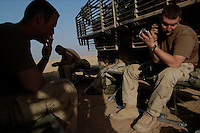 Soldiers with B Co. 3/21 go through their morning rituals in the desert near the Syrian border. Saturday July 16, 2005.