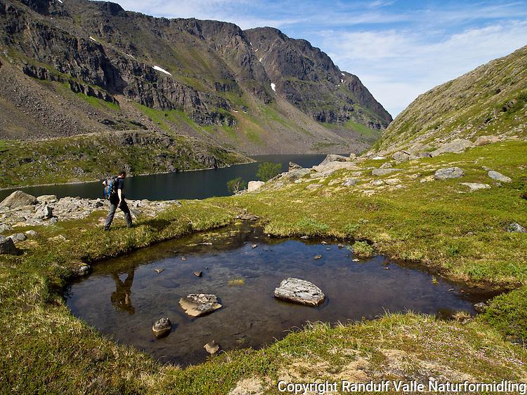 Mann går til fots med Øvrevatnet på Seiland i bakgrunnen. ---- Man hiking on Seiland.