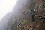 Backpacker on the edge of Phantom Terrace in the clouds, Sangre de Cristo Wilderness, San Isabel National Forest, Colorado