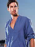 Fashion portrait of a young man wearing a blue shirt against blue twilight sky