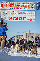 John Dixon and team leave the ceremonial start line at 4th Avenue and D street in downtown Anchorage during the 2014 Iditarod race.<br /> Photo by Jim R. Kohl/IditarodPhotos.com
