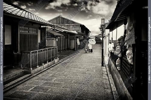 Black and white city scenery of a Couple with Japanese parasols wearing traditional kimono walking down an old street, Yasaka dori, near Kiyomizu-dera in Higashiyama, Kyoto, Japan 2017.