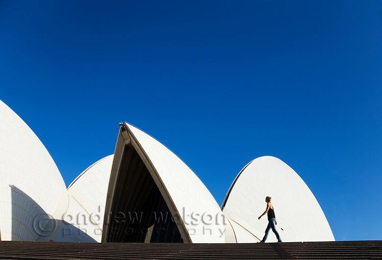 A woman walks the steps of the Sydney Opera House.   Sydney, New South Wales, AUSTRALIA.