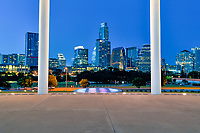 Austin Long Center Twilight - This is the Austin skyline through the pillars of the Long Center in downtown along Lady Bird Lake. The long center for the performing art was name after Joe R. and Teresa Lozano Long who contributed 20 million dollar toward the project. Because of cost the Long Center for the performing arts had to be completed in phases and it was officially completed after ten years in March 28 2008. This is a favorite place for people to come and look at the Austin skyline. We like the way the pillars frame up the city cityscape with the lighted pillars. The Long Center used 95% of recycle material from the orginal Palmer Event Center to complete the phase 1 part of the project. Phase I of the building project included the Michael & Susan Dell Hall and the Debra & Kevin Rollins Studio Theatre. The building is a circular structure with a large pavillian with this beam around held up by pillars for very unique architecture.