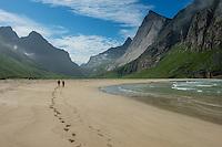Two hikers leave footprints in sand at Horseid beach, Moskenesøy, Lofoten Islands, Norway
