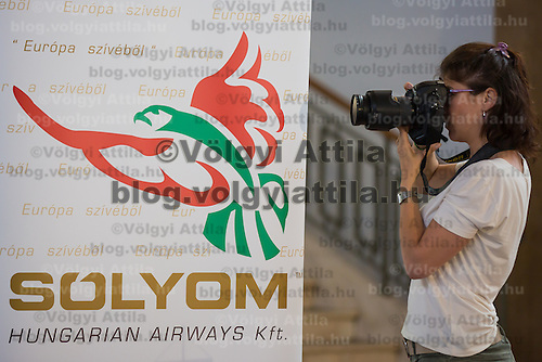 Photographer takes a picture during the press conference of Solyom Airways in Budapest, Hungary on July 24, 2013. ATTILA VOLGYI