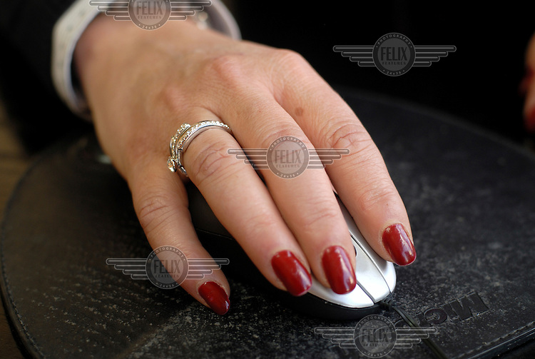 A woman's hand with painted nails using a computer mouse.