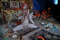 A Naga Sadhu (naked saint) in a yoga posture at Juna Akhara tent at Kumbh mela on 13th February 2010. Haridwar, Uttara Khand, India, Arindam Mukherjee
