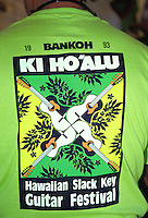 Person wearing green shirt with logo at the Hawaiian slack key guitar festival on Oahu