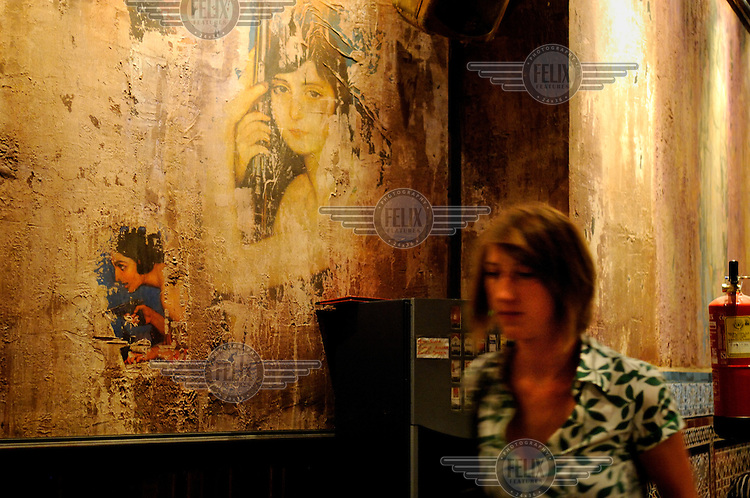 A woman passes old decorations on the wall of a tapas bar close to Plaza de Santa Ana.