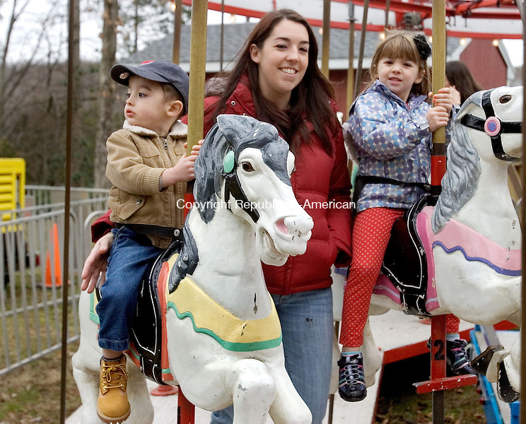 WOLCOTT, CT. 09 December 2012-120912SV05-Mylesia Mascolo of Wolcott ride a merry-go-round with her children, Joseph, 2, and Emily, 4, at the annual winter wonderland run by the Lions Club in Wolcott Sunday..Steven Valenti Republican-American