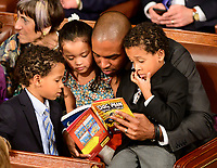 United States Representative Antonio Delgado (Democrat of New York) reads to his children from his seat as the 116th Congress convenes for its opening session in the US House Chamber of the US Capitol in Washington, DC on Thursday, January 3, 2019. Photo Credit: Ron Sachs/CNP/AdMedia