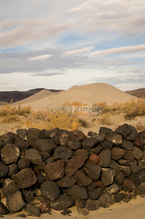 Rock wall and sand dunes in Central Nevada Valley along Highway 50 near Fallon, Nevada.