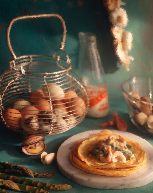 Seafood pancakes being made in a blue kitchen with a basket of eggs behind