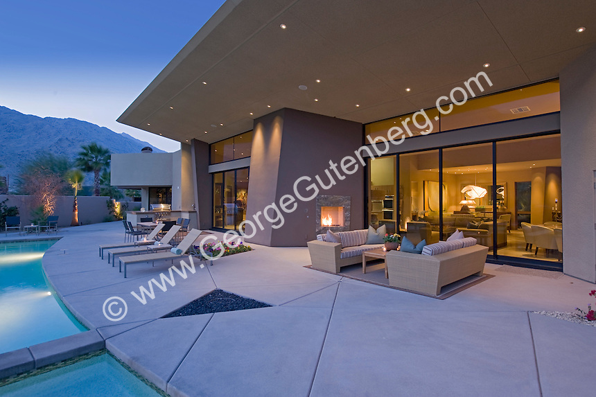 Outdoor living areas at ultra modern home shown at dusk
