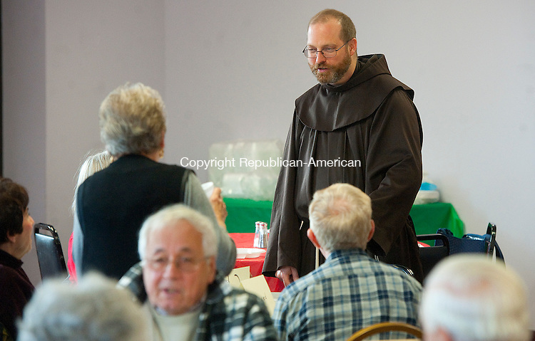 WINSTED,  CT-122816JS01-- Father Chris Gaffrey, Pastor at St. Joseph Church in Winsted, welcomes guests during Wednesday's senior parishioners luncheon held at the St. Joseph Church Parish Center in Winsted.  More than 70 parishioners attended the luncheon, which is held twice a year, and is made possible through a grant through the Cooperative Parish Sharing, Social Justice<br /> Ministry of the Archdiocese of Hartford.<br /> Jim Shannon Republican-American