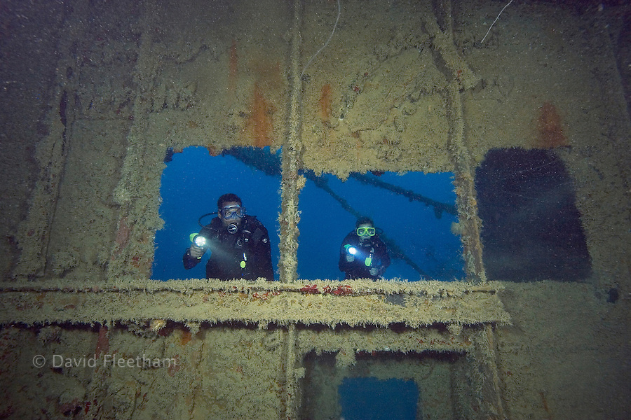 Divers (MR) looking into a large wreck, Palau, Micronesia.