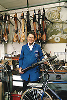 Switzerland. Canton Zoug. Steinhausen. Mr Anton Ruegg, an elderly man, works as a bicycle reseller, but he also makes crossbows in his shop. On the wall is painted William Tell, the legendary figure and a swiss national hero. © 1989 Didier Ruef