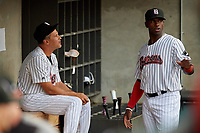 Birmingham Barons manager Omar Vizquel (13) talks with Luis Robert (26) before a Southern League game against the Chattanooga Lookouts on May 1, 2019 at Regions Field in Birmingham, Alabama.  Chattanooga defeated Birmingham 5-0.  (Mike Janes/Four Seam Images)