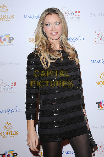 CAPRICE BOURRET.Attending The Noble Gift Gala, Dorchester Hotel, London..13th March 2010 .half length black dress clutch bag striped stripes long sleeves tights .CAP/BEL.©Tom Belcher/Capital Pictures.