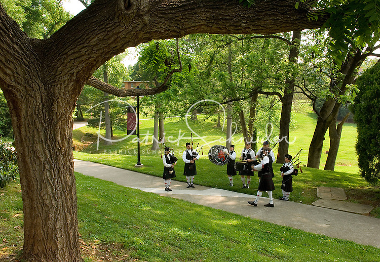 A bagpipe and pipe and drum band warm up in the shade of a large tree on campus during Graduation Ceremony at Belmont Abbey College in Belmont, NC.