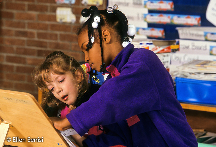 MR / Schenectady, New York.  Zoller School (urban public elementary school). Grade 1 Inclusion classroom. Girl (6, African-American) helps student (girl, 6, cerebral palsy working at adaptive desk) at independent work time. ID: MF. MR: Her4, All5 ©Ellen B. Senisi