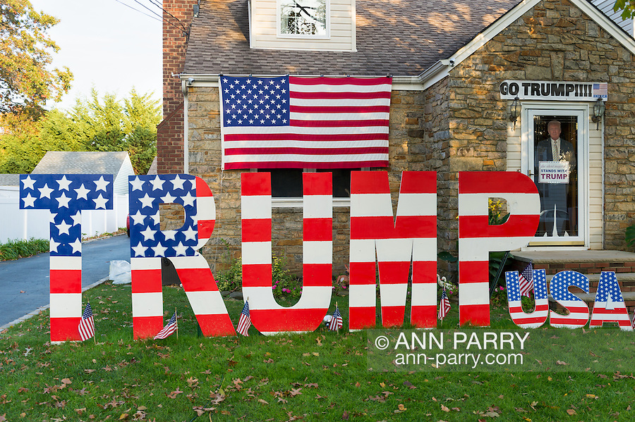 """Bellmore, New York, USA. November 2, 2016. Large letters spelling TRUMP, and many other colorful pro-Trump displays are in Halloween front yard display of Eileen Fuscaldo, a supporter of the Republican presidential candidate Donald Trump. On her front door is a life-size cardboard Trump holding """"The Silent Majority Stands with Trump"""" sign."""
