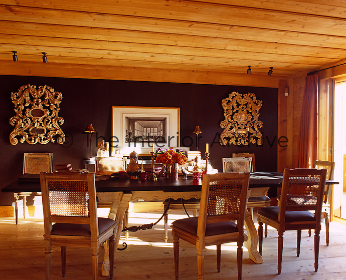 The dining room is furnished with a long extending table and wicker-backed dining chairs