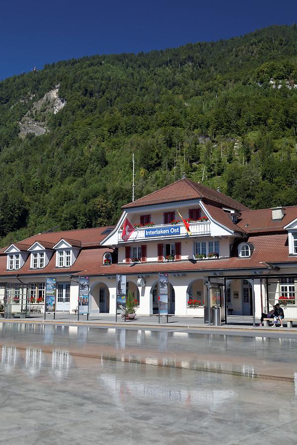 Interlaken Ost or Interlaken East railway station reflected in pool, Interlaken, Switzerland