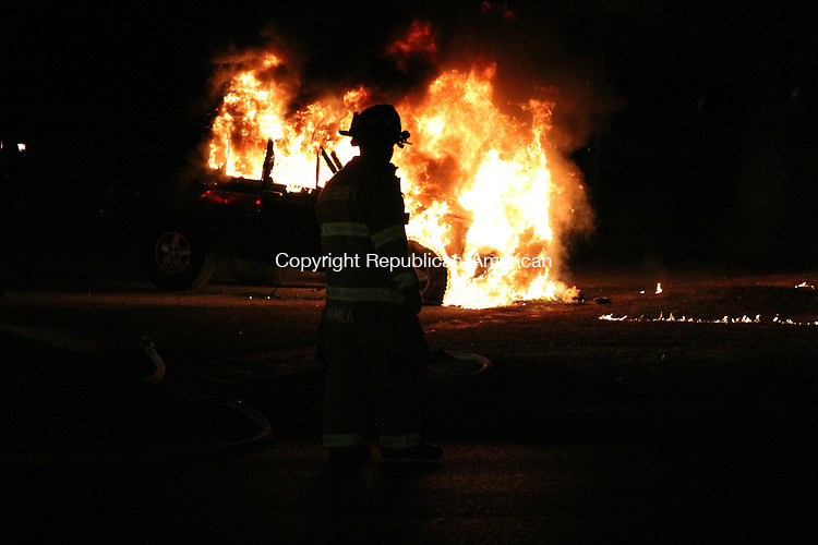 SOUTHBURY, CT: 10 Dec. 2015: 10122015CB02: SOUTHBURY -- A firefighter prepares to battle a vehicle blaze Thursday in Southbury at the Subway parking lot on Oak Tree Road near the intersection of Main Street South. Caleb Bedillion Republican-American