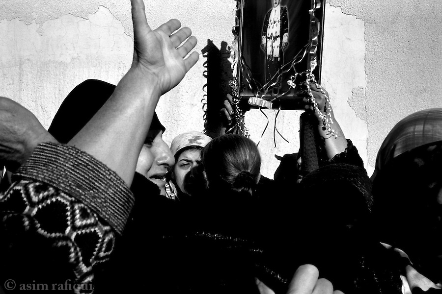 dohuk, northern iraq,january 2005: on the 3rd day of mourning, traditionally when the family is allowed to grieve the dead, women hold up a portrait of isaac sheba slewa who was killed by iraqi islamic insurgents/resistance fighters while on his way to mosul.<br />