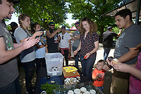 NWA Democrat-Gazette/BEN GOFF @NWABENGOFF<br /> Daniel Zalsman, a cook at Pressroom, shows Kelsey Ferguson, bartender at Preacher's Son, how to shuck clams Sunday, May 21, 2017, during a field day for employees of RopeSwing Hospitality Group and their guests at the Rios family farm in Little Flock. RopeSwing Hospitality Group, which operates Pressroom, The Preacher's Son, Undercroft, and Record in downtown Bentonville, has been active in sourcing regional food and supporting the farm-to-table movement. The social event was a chance for their staff to roll up their sleeves and connect with their supplier by helping out on the farm. Rafael Rios, owner and chef of Yeyo's Mexican Grill food truck, and his family have had a presence at the Bentonville Farmers Market over the past decade, but are shifting their focus this year to supplying local restaurants.